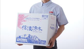 信濃湧水の水が入った箱を持つスタッフ